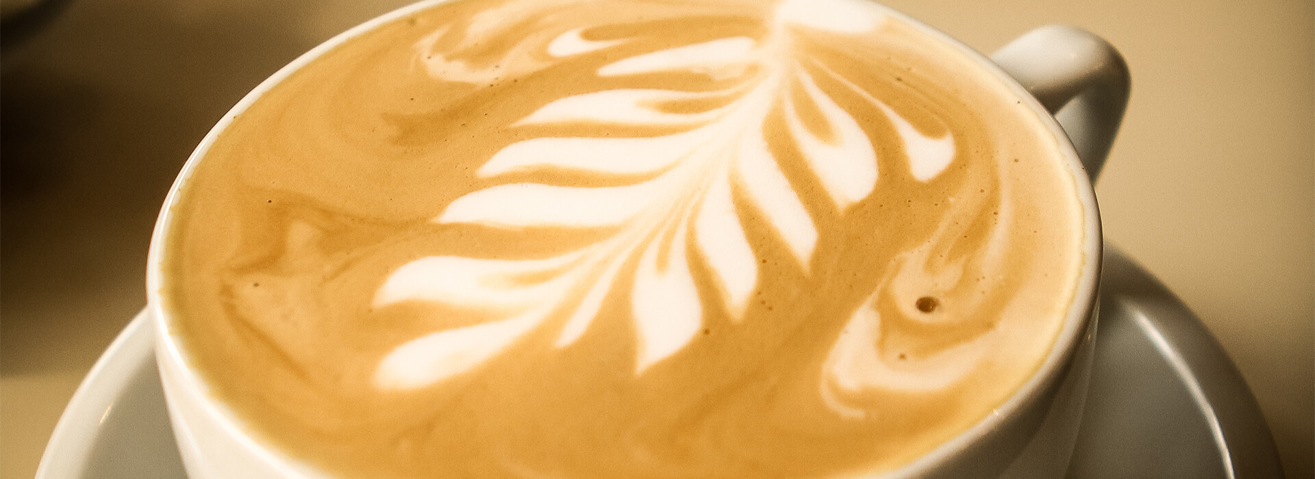 A beautifully decorated cup of coffee with a foam leaf.